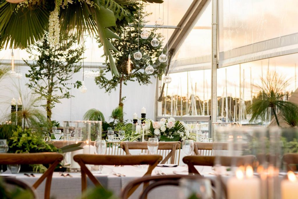 Beautiful white-themed dinner table setup for a wedding with white roses and lots of plants