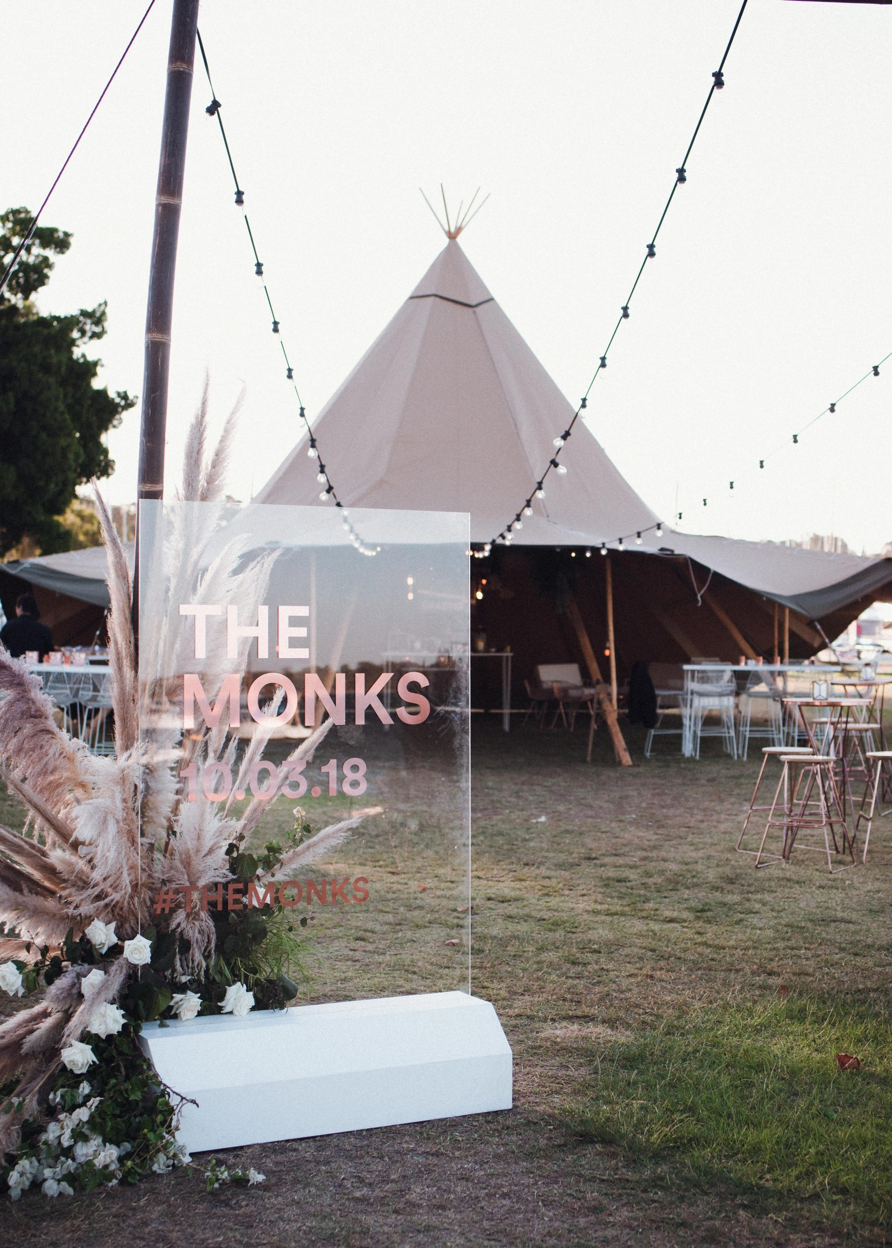 Party setup in the Riverside Lawn with an old rose tent standing on it, chairs setup and a beautiful outdoor string lights