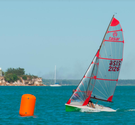 Two aduts navigating a tasar on the sea and a floating orange buoy
