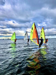 Four windsurfers sailing on the sea