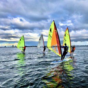 Four windsurfers sailing on the sea