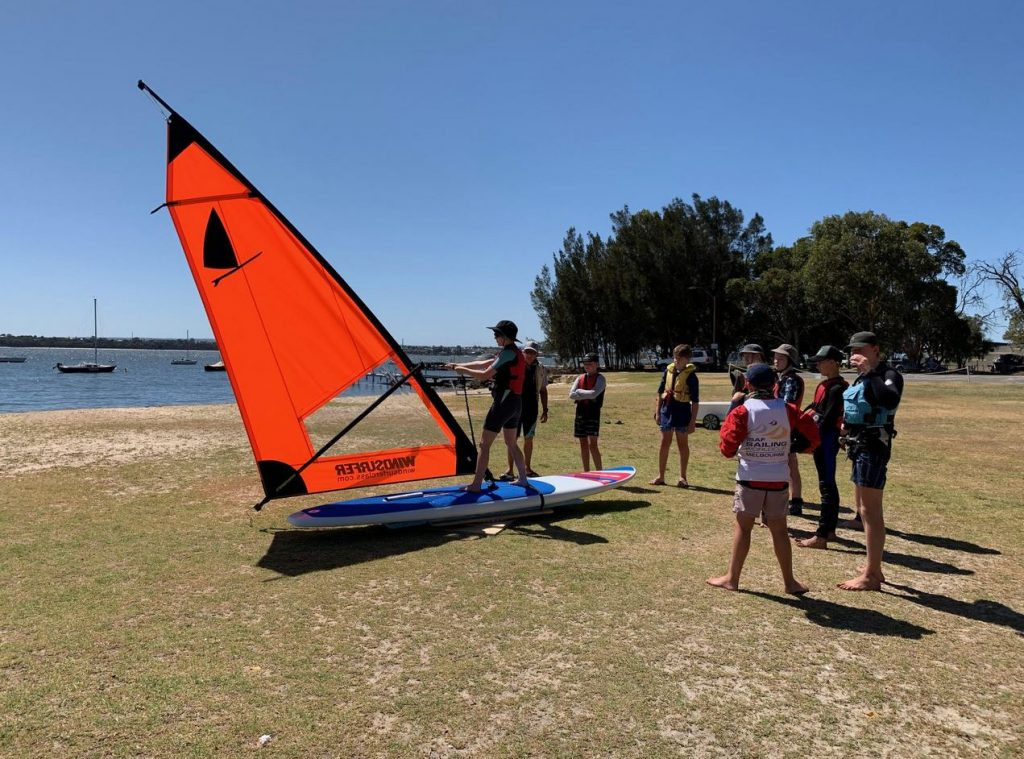 A kid trying out a Windsurfer LT on land with a bunch of kids on the side and a trainer